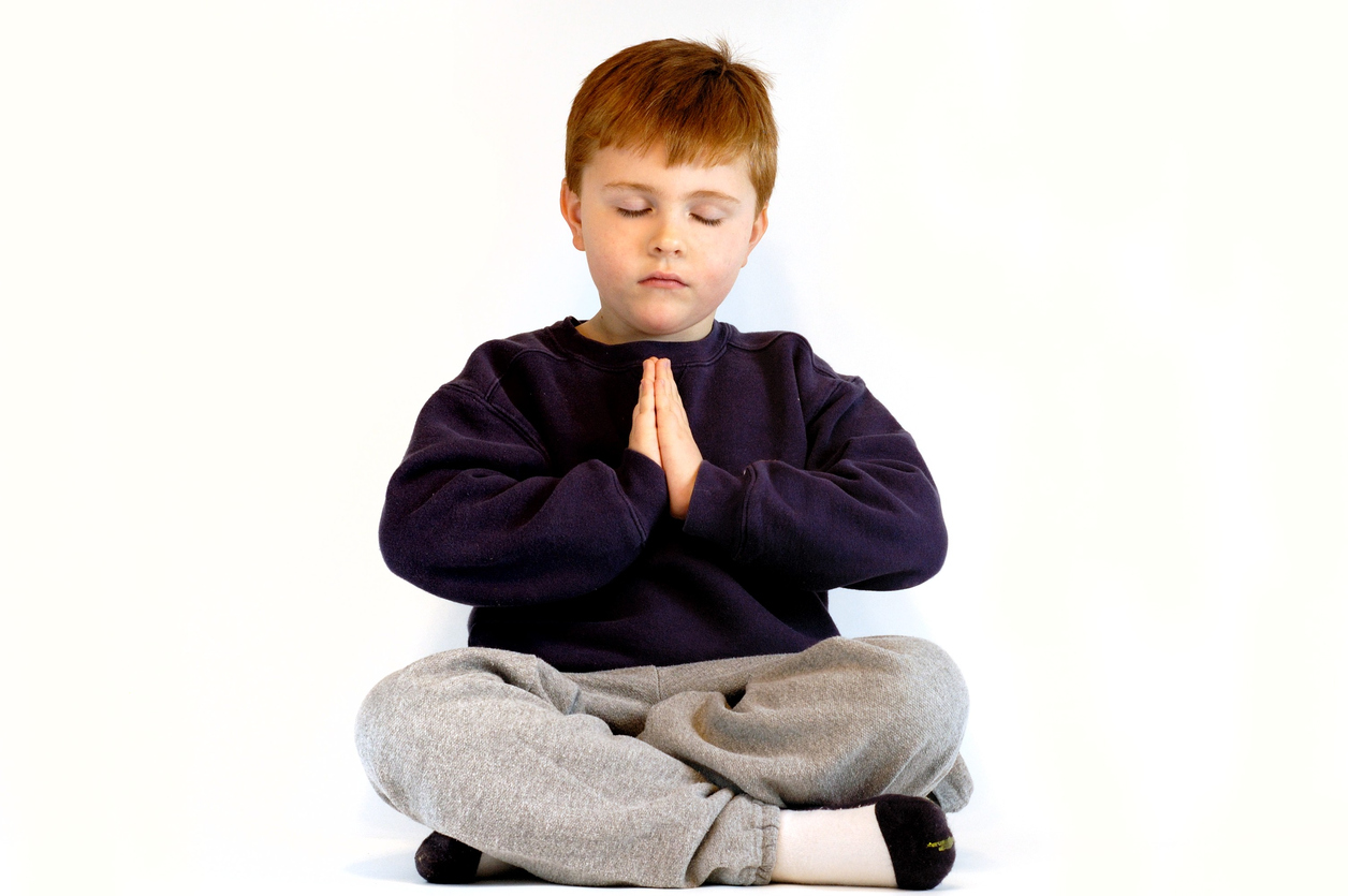 small boy meditating or praying